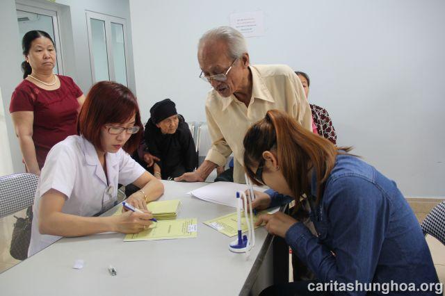 Nhân viên của bệnh viện đón tiếp và phát sổ khám bệnh cho các bệnh nhân
